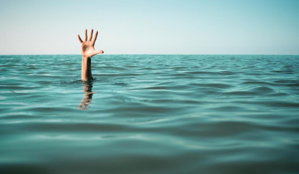 The hand of a person drowning in the middle of the ocean (sink or swim).