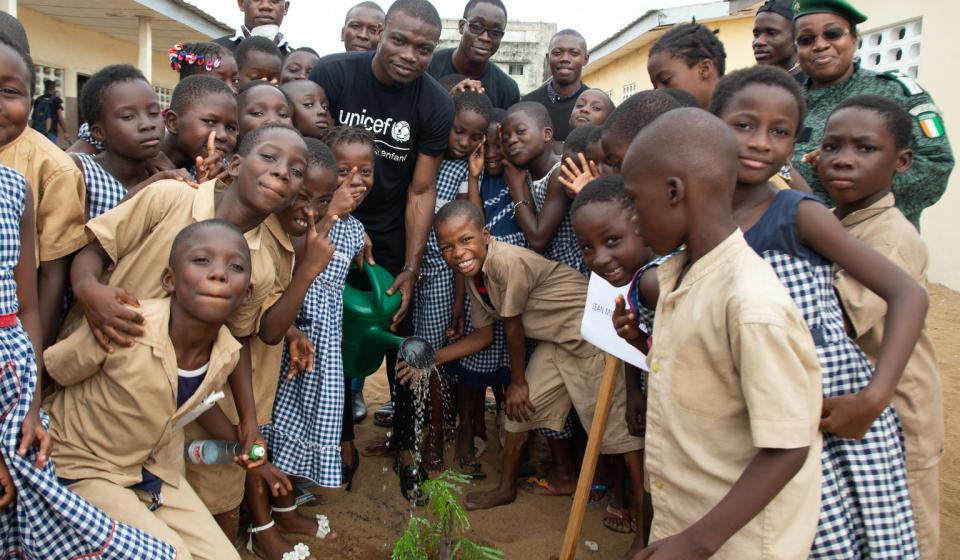 A group of students plant a tree in their school yard.