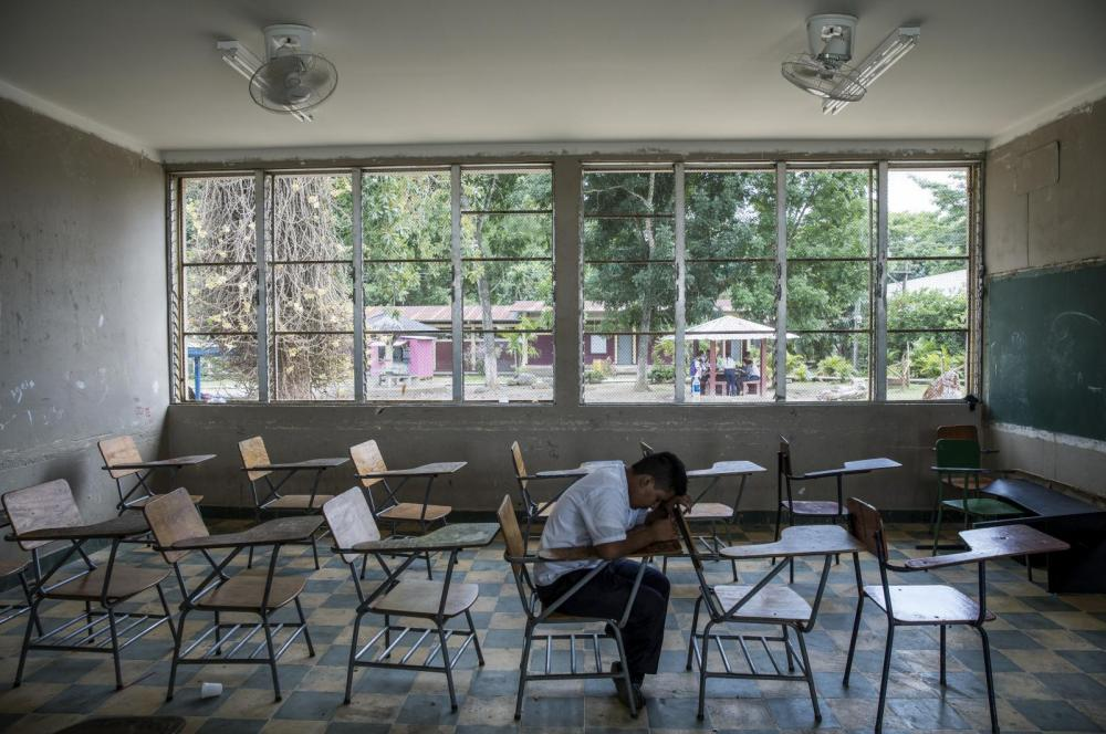 A child sits in an empty classroom with his head on his desk.