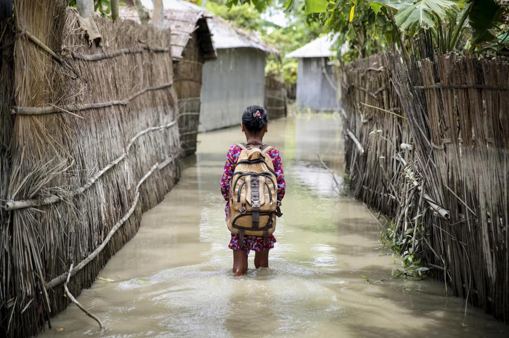 A young girl standing in a flooded area with homes wearing a backpack.