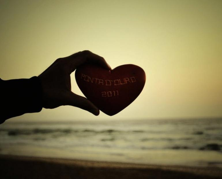 A silhoutted hand holds a heart-shaped object against the ocean.