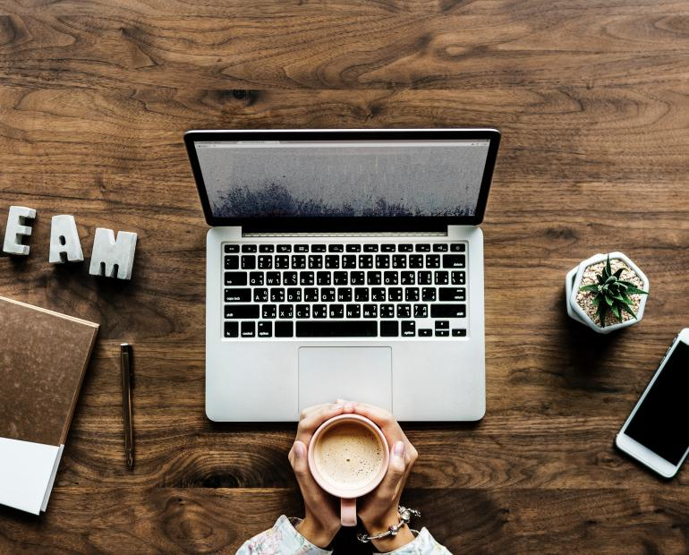 A photo shot from above showing an open laptop and two hands holding a coffee mug in front of it.