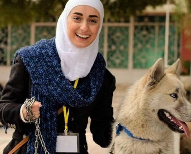 Salam Al-Nukta, smiling, standing next to a dog