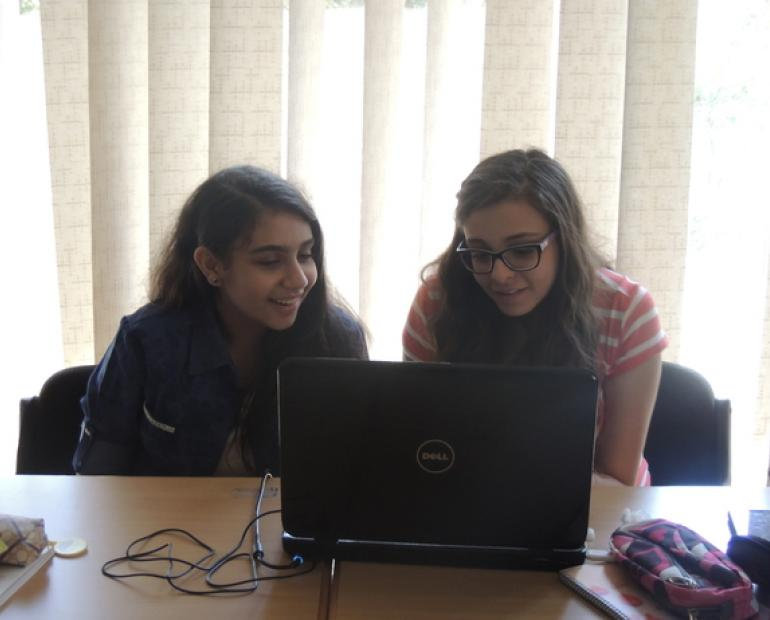 Two young women sit in front of a laptop.