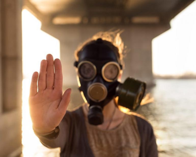 A person in a gas mask holds up their hand to the camera.