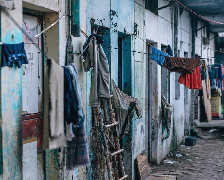 Clothes hang on a line outside a house.