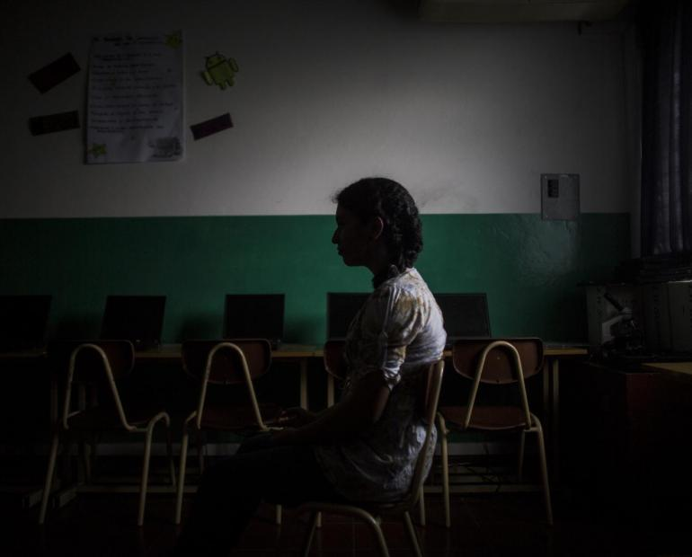 A girl sits in a dark room