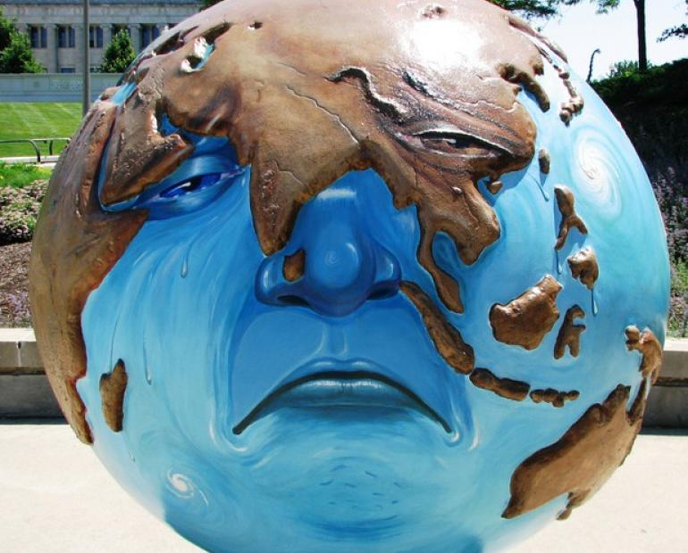 A sculpture of a sad planet earth.