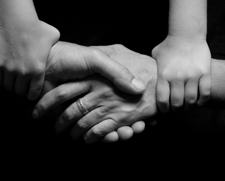 Hands holding hands, black-and-white image