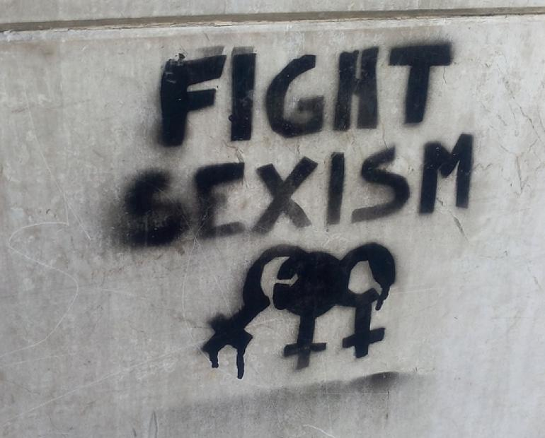 "A sign on a wall saying ""Fight Sexism"""