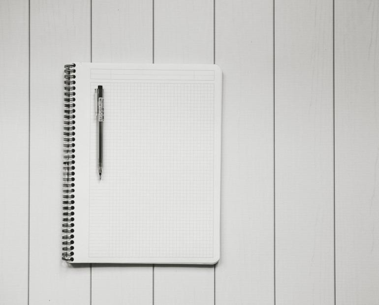 Blank paper notebook with a black pen resting on it.