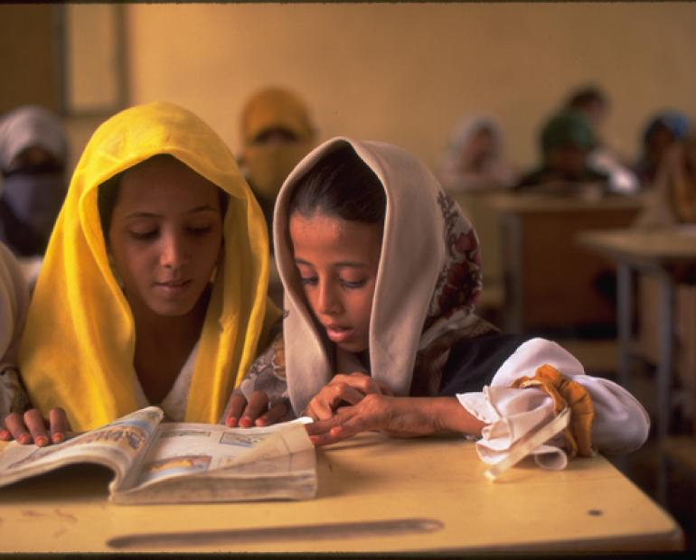 two girls share a book in a class at the local primary school in the village of Kwanawis