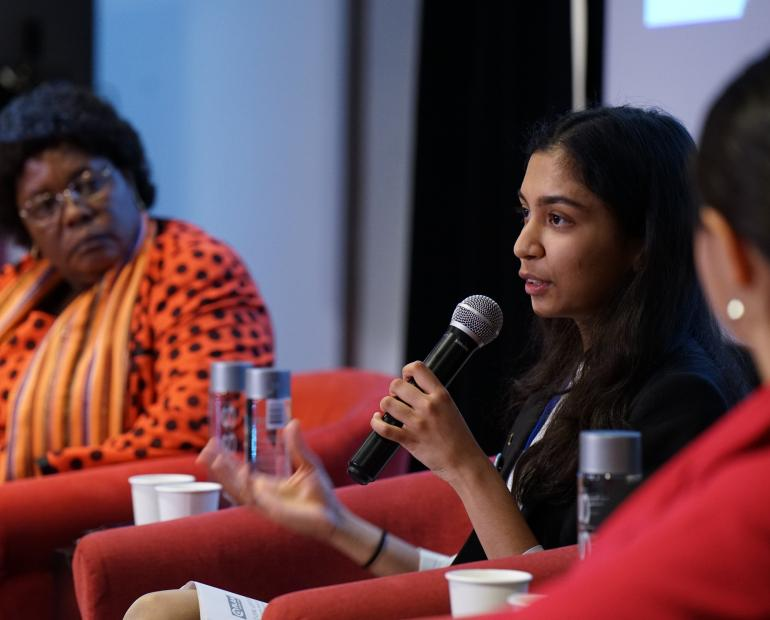 A young woman speaks on a panel on gender equality.