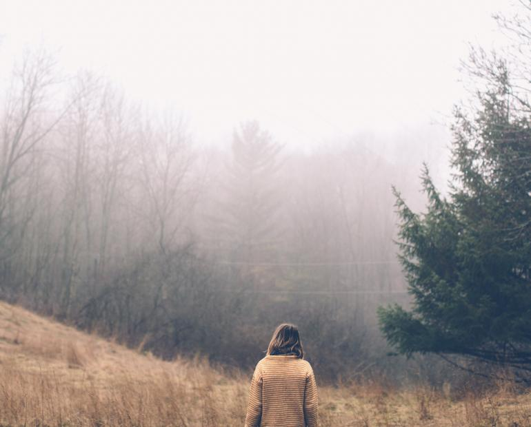 A woman facing a foggy forest.