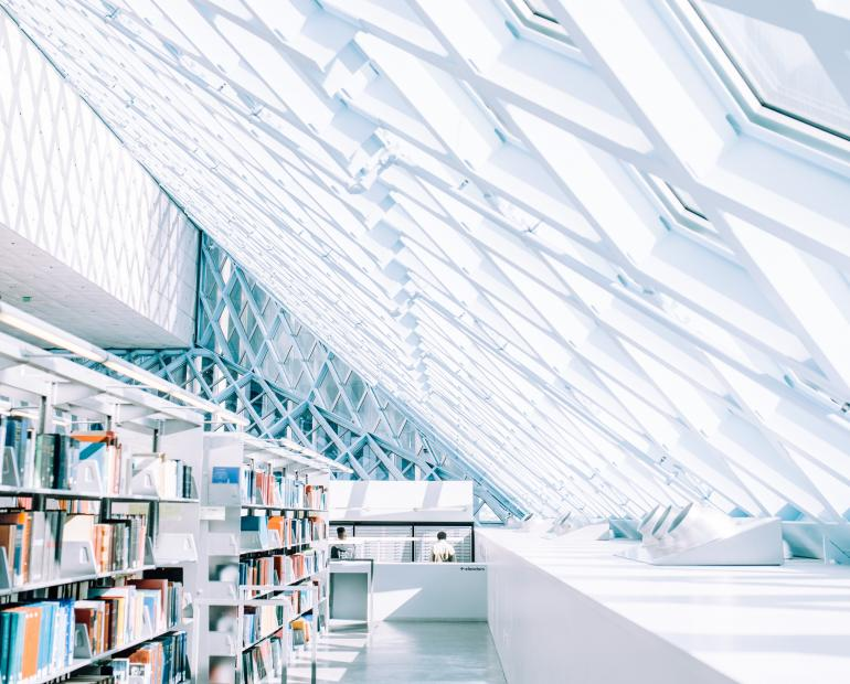 White shelves with books in a library with a futuristic appearance