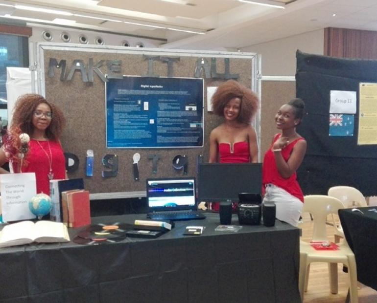 Three girls showcasing their digital repository site at an exhibit.