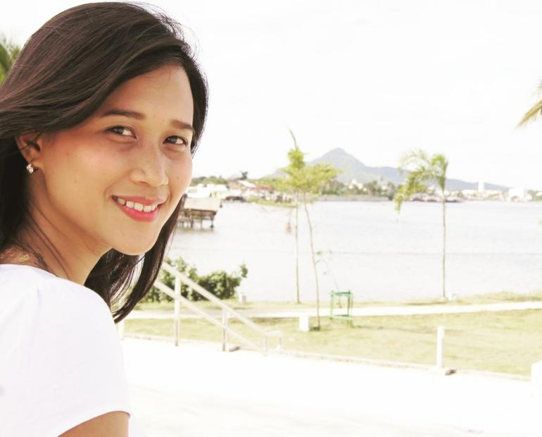 A young woman turns to look at the camera smiling. She is in front of water, mountains and palm trees.