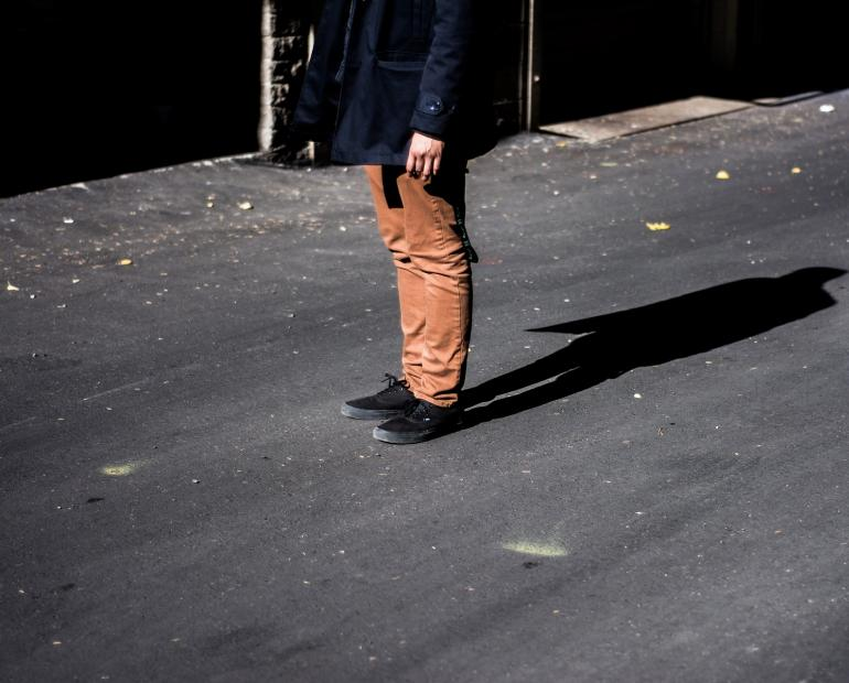 Image of legs of a boy who is wearing brown trousers.