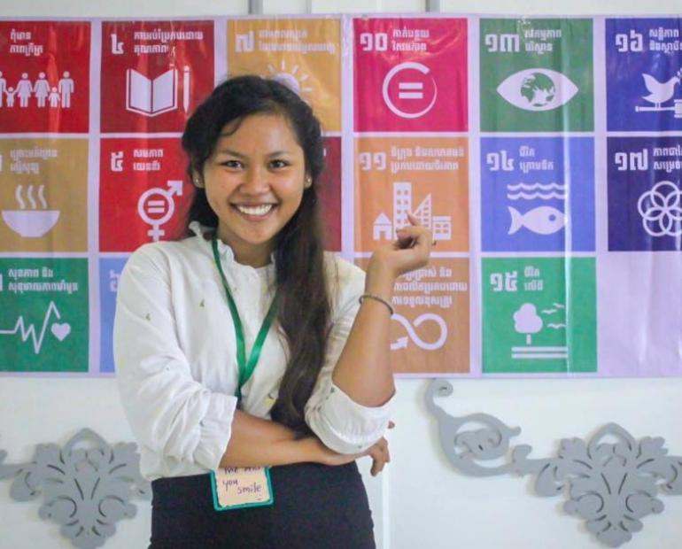 Manin standing in front of the SDG icons smiling.