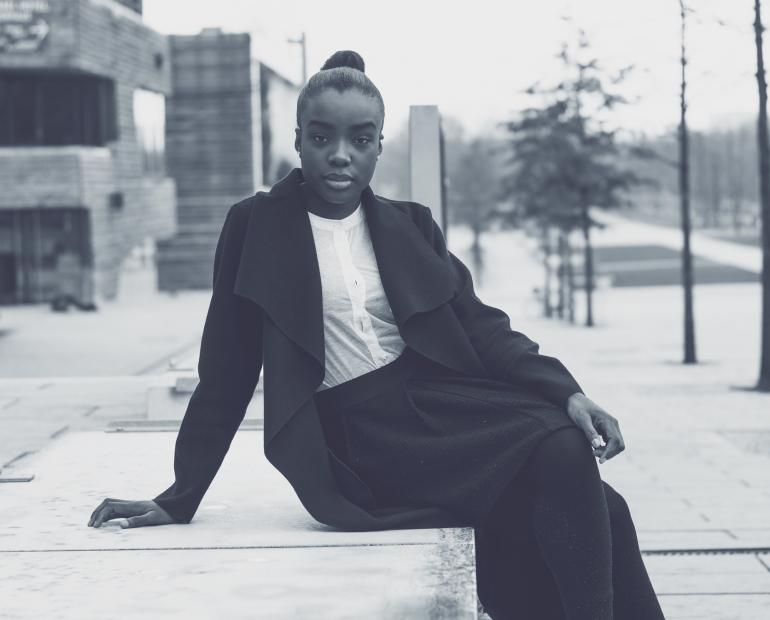 A black woman sits on a cement barrier in an urban setting, looking into the camera.
