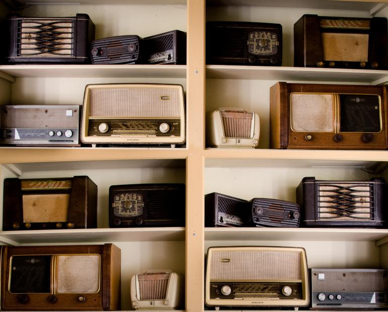 A shelf with lots of old radio sets displayed on it.
