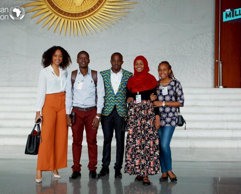 Youth Delegates from Tanzania standing at AU HQ building