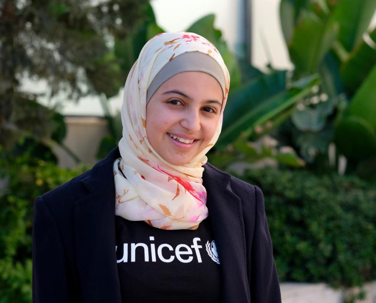 A close up shot of Muzoon smiling wearing a UNICEF t-shirt.