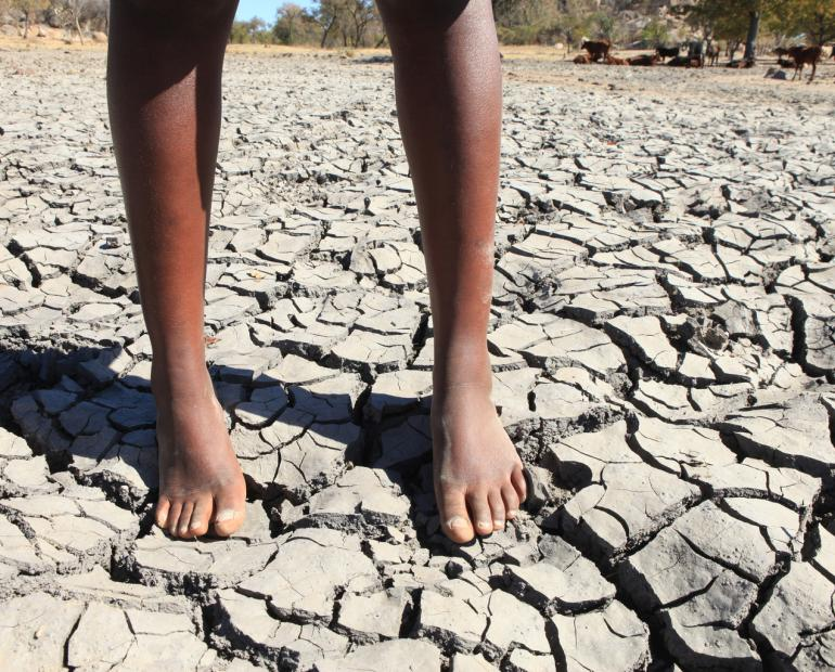 A close up of a young boys legs standing on top of dry and cracked mud.