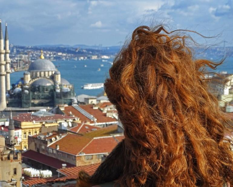 A girl admiring the Bosphorus while her long red-brown hair flies in the wind,