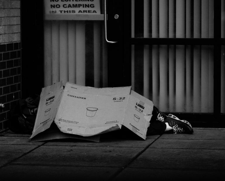 A black & white photo of a person laying under a cardboard box on the streets