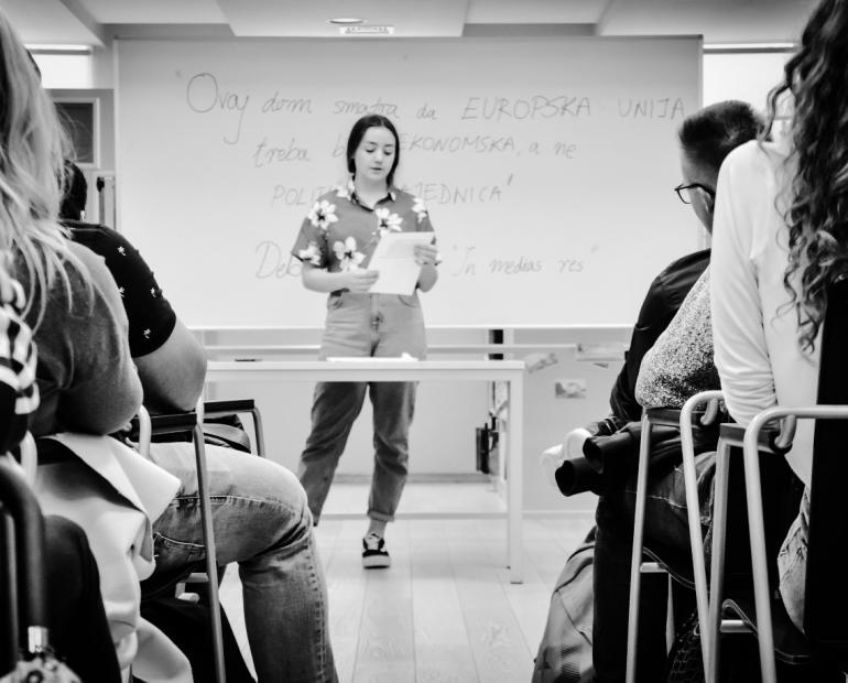 A young woman stands in a classroom reading from a piece of paper