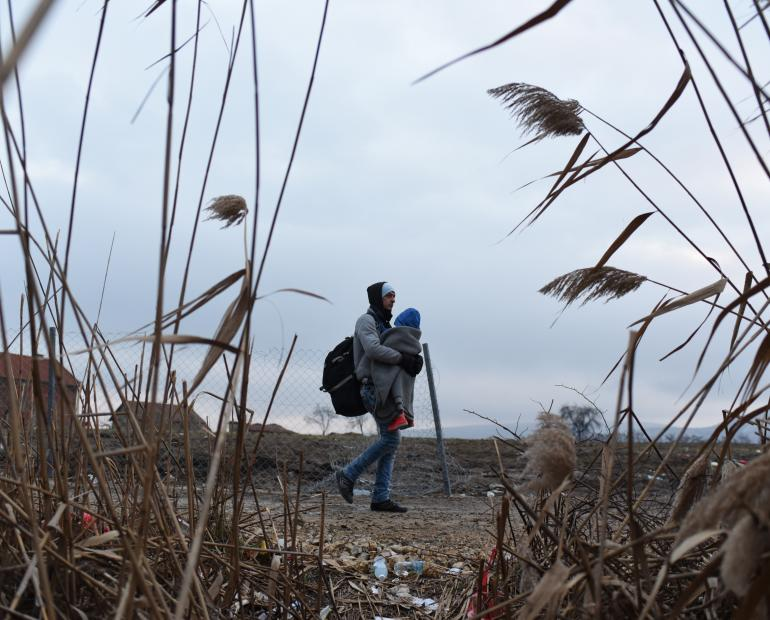 A father carries his son, making their way on foot to the Serbian border. They have a 2-km walk to reach the next refugee and migrant registration point in Serbia.