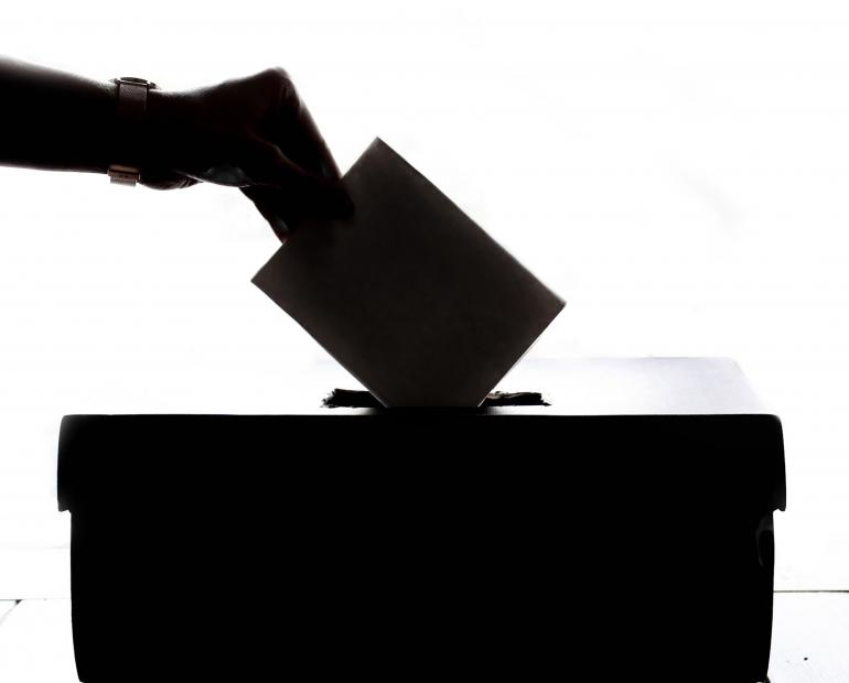 A silhouette of a person casting a vote