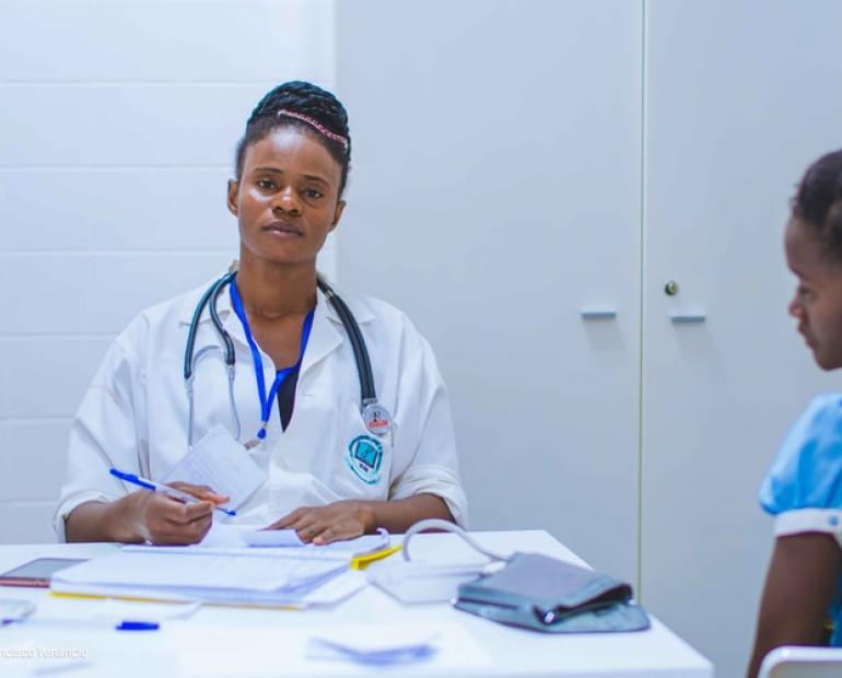 Image of an African American female doctor sitting with a patient and filling out paperowrk