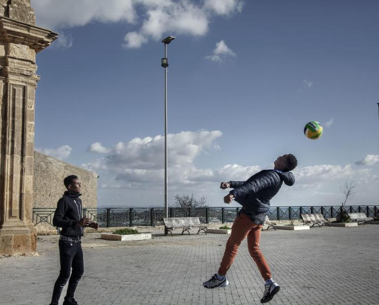 Two young men play football outdoors in an Italian town.