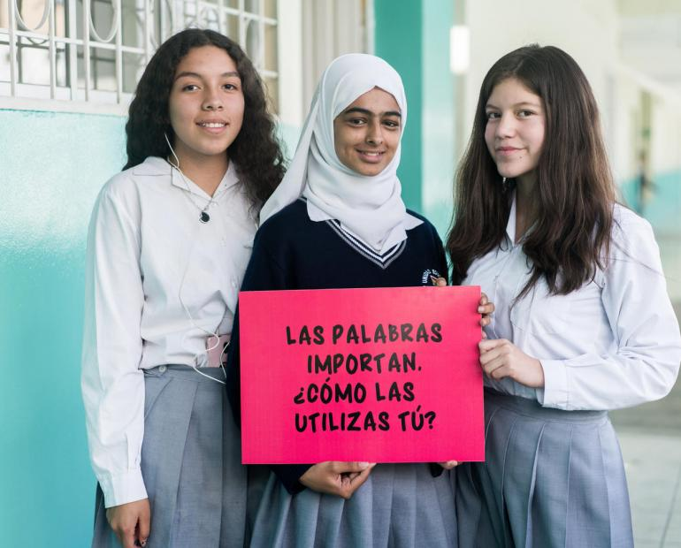 A group of three students in Ecuador with a sign that reads: Words Matter. How do you use them?