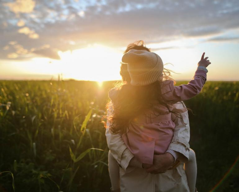 girl and mother in field at sunset