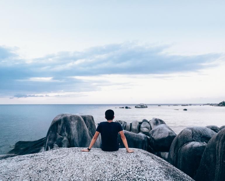 A man sits on a rock overlooking the ocean.