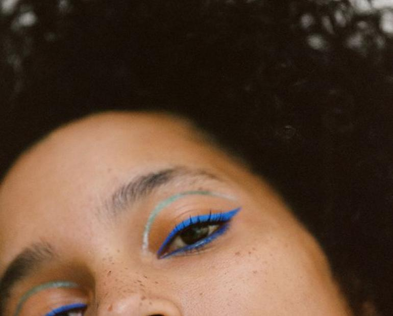 a woman with curly hair and a blue and orange eye shadow look. she is looking at the camera.