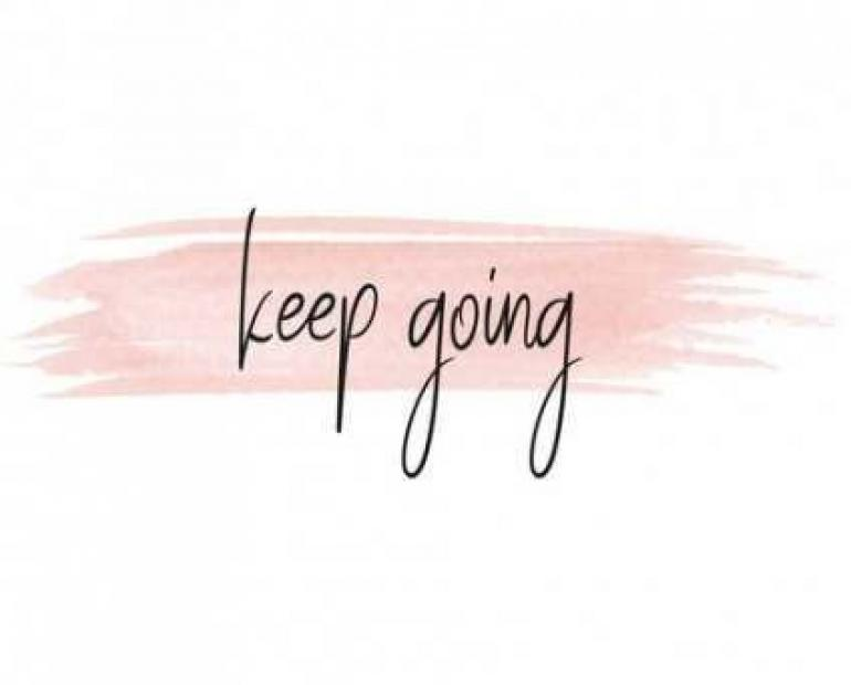 "The words ""keep going"" on top of pink marker on white paper."