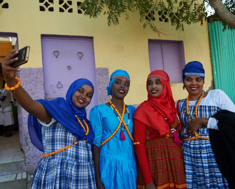 Four young Djiboutian girls clad in their traditional attire pose for a photo.