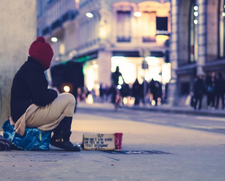 Person sitting on the street covered with a blanket near a cardboard sign asking for help
