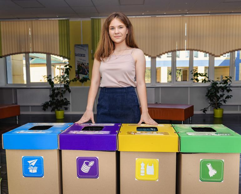 Yana stands with trash cans for different waste materials.