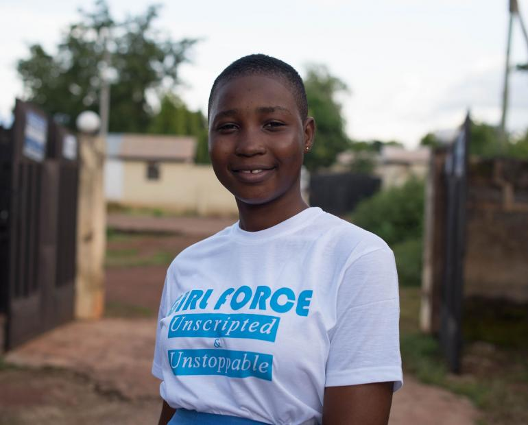 "Alidu smiling outside wearing a t-shirt that says ""Girl force: Unscripted and unstoppable"""