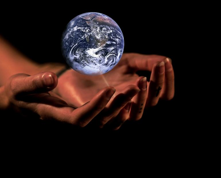 two hands holding a holographic image of planet earth
