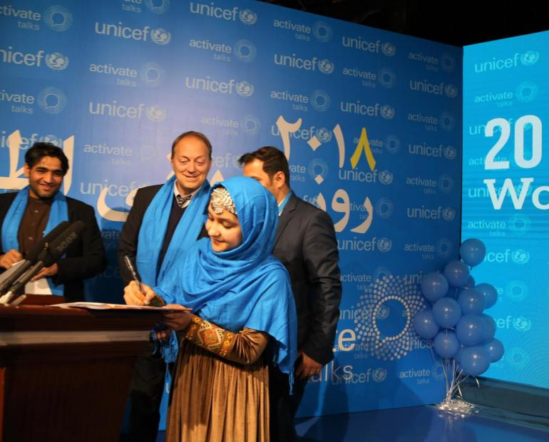 Hinna signing a piece of paper at a UNICEF event.