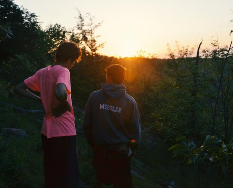 Two young people, one wearing a pink shirt, one wearing a green shirt, staring at a field overlooking the sunset