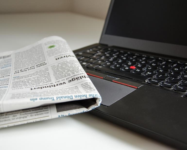 A newspaper and a laptop
