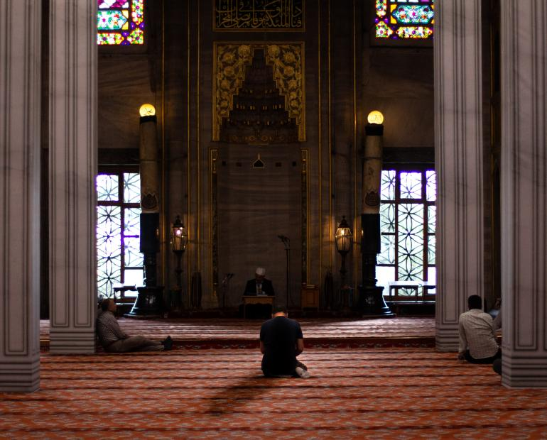 A man praying into a mosque.