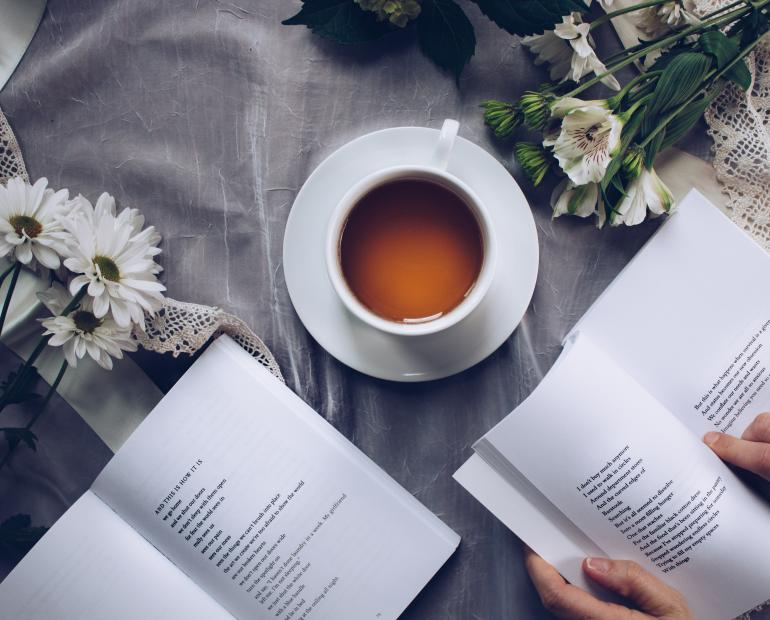TWo open books and a cup of tea on a table. There are also flowers on the table. The photo is taken from above.